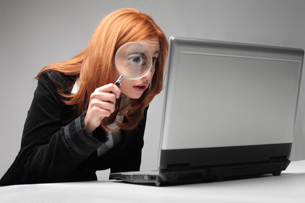 Dame som søker med forstørrelsesglass på pc
