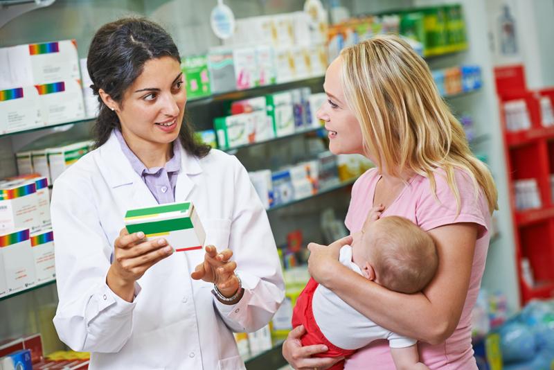 Bilde fra apotek. Apoteker veilder mor med baby
